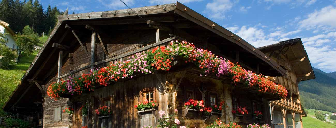 Farm made of wood with geraniums on the balcony