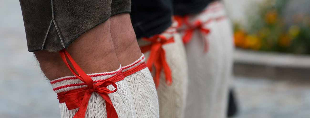 Closeup of legs of men in the typical South Tyrolean costume