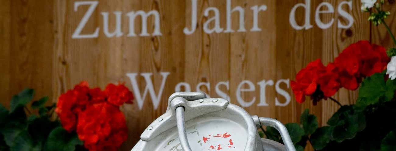 Water canister with wooden font decorated with red Geraniums