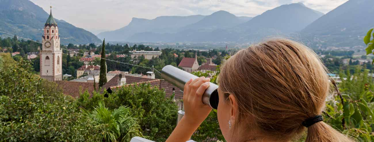Girl look with a telescope at the Church of St. Leonhard