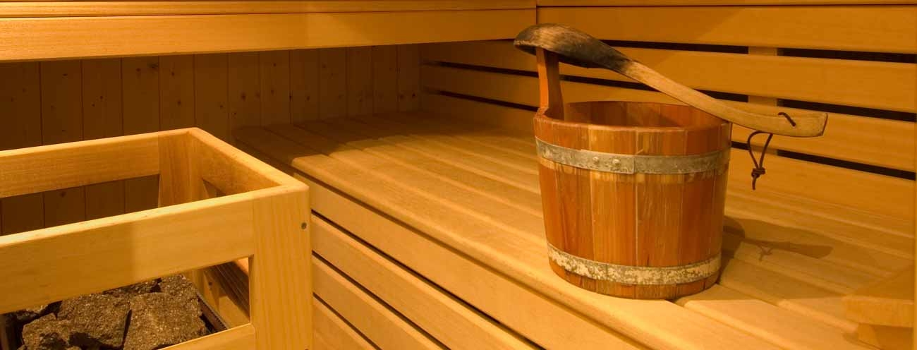 Close up of the water bucket and the benches of the sauna in Königsrainer